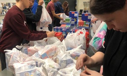 Indian Hill High School students pack 4,000 sacks of food before the holidays